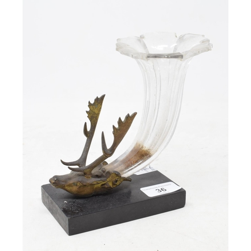 36 - A 19th century glass cornucopia vase, mounted in a bronze stag's head, on a black slate base, chippe...