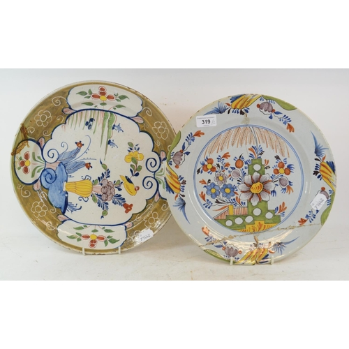 319 - A Dutch polychrome Delft plate, decorated a vase of flowers and a bird, 33.5 cm diameter, and anothe...