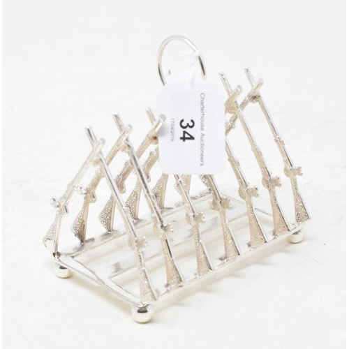 34 - A plated toast rack, in the form of crossed guns, 11.5 cm high...