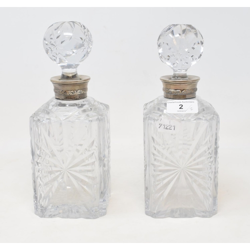 2 - A pair of cut glass decanters, with French silver coloured metal collars, 24 cm high (2)...