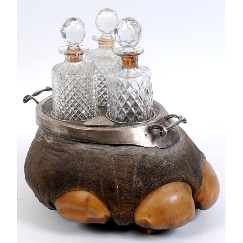 21 - An Edwardian silver mounted elephants foot three bottle tantalus, with two built in snuff boxes, a s...