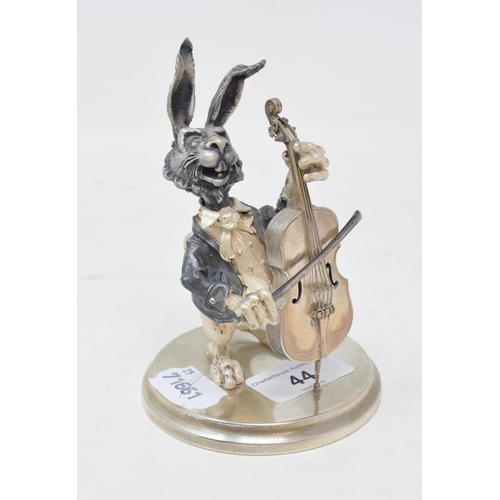 44 - A burnished and silver coloured metal amusing figure, of a hare playing a cello, on a circular base,...
