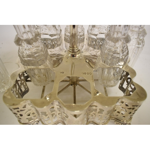 8 - A Victorian silver and cut glass eight piece cruet, crested, of shaped outline, with pierced decorat...