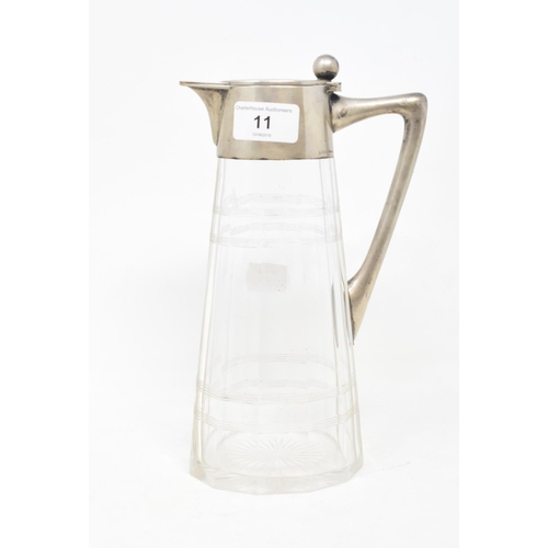 11 - A Continental glass and silver coloured metal mounted claret jug, stamped .800, 25.5 cm high...