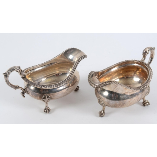 128 - A pair of early 19th century silver sauce boats, with leaf capped scroll handles, on claw and ball f...