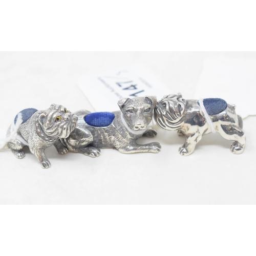 147 - Three silver dog pincushions...