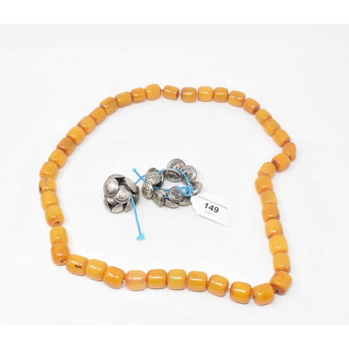 149 - Assorted Malayan and other silver coloured metal buttons, and a string of amber type beads...