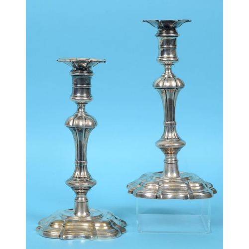 174 - A pair of George II cast silver candlesticks, with detachable sconces, on spreading shaped square ba...