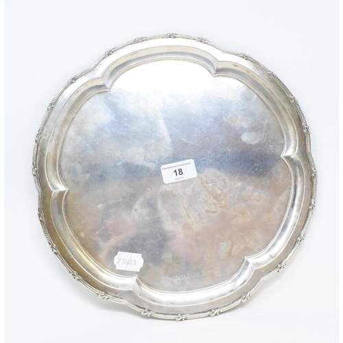 18 - A silver salver, of shaped circular form, with a bead and scroll border, Birmingham 1931, approx. 24...