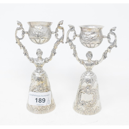 189 - A pair of Continental silver coloured metal wager cups, with embossed decoration, 14 cm high...