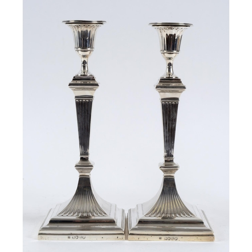213 - A pair of Victorian silver table candlesticks, of fluted form, on spreading square bases, London 188...