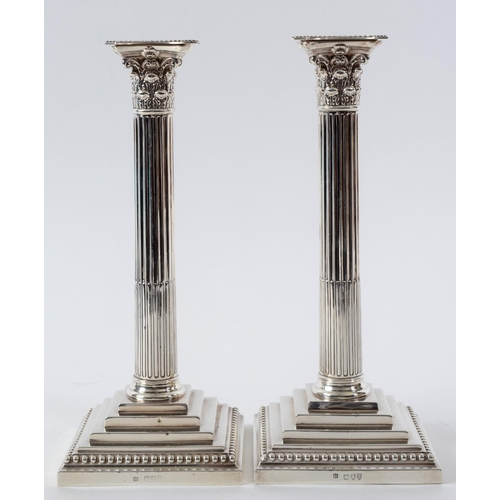 214 - A pair of late Victorian silver Corinthian column table candlesticks, on stepped square bases with b...