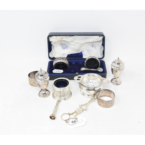 249 - A silver tea strainer and stand, pair of silver pepperettes, two silver napkin rings and other items...