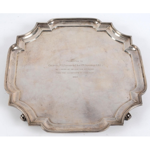 27 - A silver salver, of shaped square form, with presentation inscription and dated 1932, on four scroll...