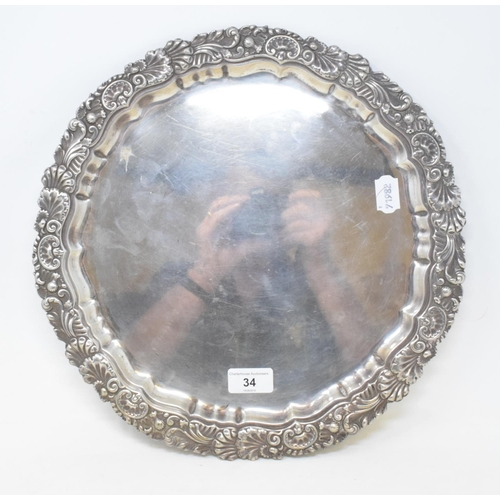 34 - A late 19th century silver salver, the border decorated foliage and shells, on three scroll feet, Lo...