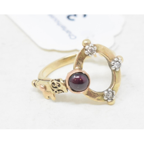 351 - A yellow coloured metal ring, in the form of a key, with a red cabochon and three diamonds...