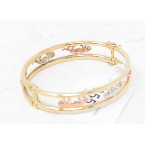 355 - A 9ct three colour gold bangle, decorated Panthers...