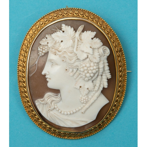 369 - A late 19th century oval shell cameo brooch, carved a bust portrait of a lady with grapes and vines ...