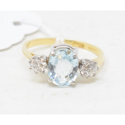 374 - An 18ct gold ring, the central aquamarine flanked by two diamonds...