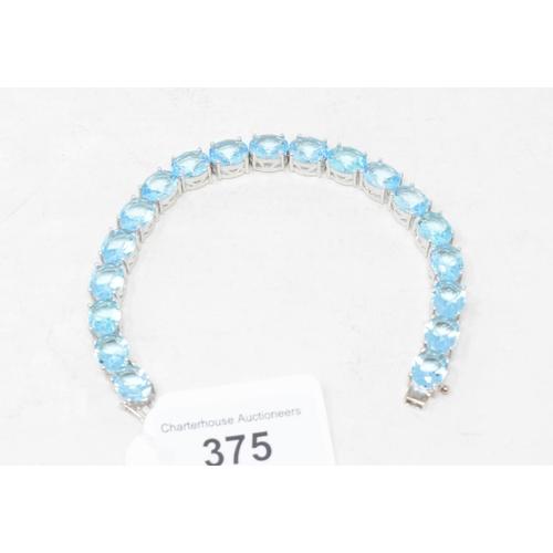 375 - A silver and blue topaz line bracelet...