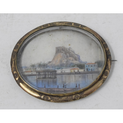 394 - An oval brooch, inset a miniature painted a landscape...