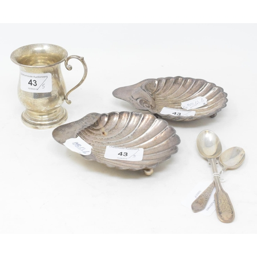 43 - A silver shell butter dish, Sheffield 1906, another similar, a christening mug, and two spoons, appr...