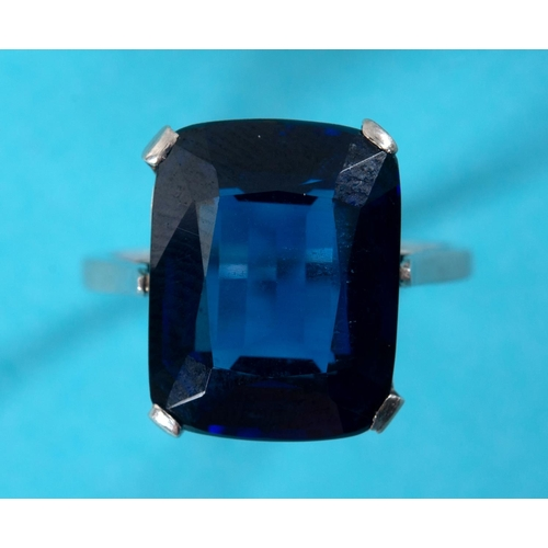 431 - A synthetic sapphire ring, in a white coloured metal mount, approx. ring size M½...