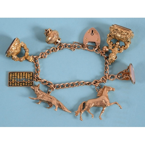 454 - A 9ct gold bracelet, with assorted charms and three seals  See illustration...