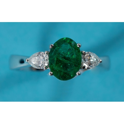 467 - An 18ct white gold ring, the central emerald flanked by two diamonds, approx ring size M See illustr...