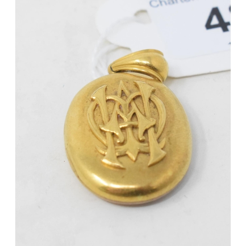 481 - A late Victorian yellow coloured metal oval locket, monogrammed...
