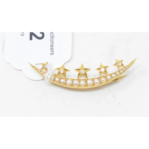 502 - A crescent brooch, set seed pearls applied five gold stars with diamond centres, yellow coloured met...