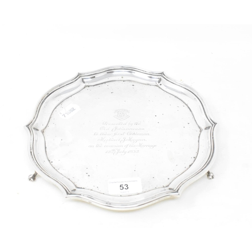 53 - A silver salver, crested, and with a presentation inscription dated 1932, on three scroll feet, Shef...