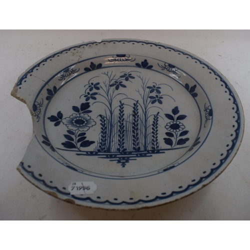 569 - A Delft blue and white pottery charger, decorated flowers, chipped, 35 cm diameter, and a blue and w...
