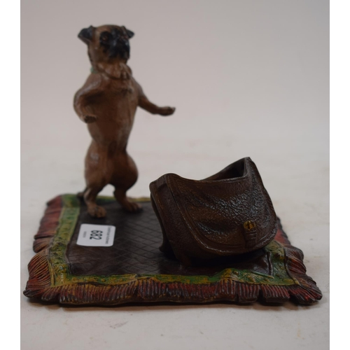 682 - A painted bronze group, in the form of a pug with a bag on a rug, 19 cm wide...