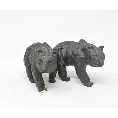 708 - A bronze figure, in the form of a bear walking, 11 cm high, and another matching (2)...