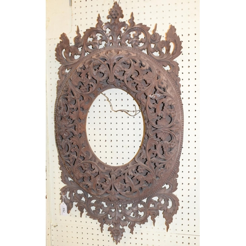 753 - Two Burmese carved hardwood picture frames, decorated flowers and scrolling foliage, of oval form, e...