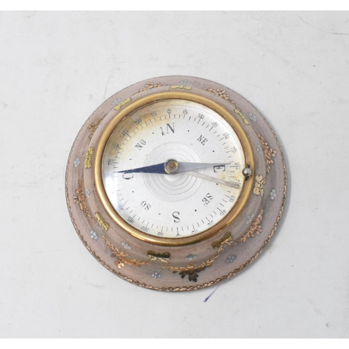 820 - A miniature desk top compass, inlaid yellow and silver coloured metal decoration, 7 cm diameter...