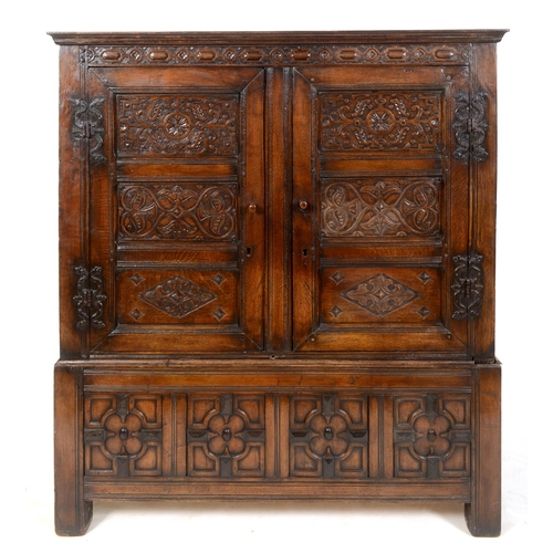 845 - An oak cupboard on stand, carved flowers and foliage, having a pair of panel doors, the base with fo...