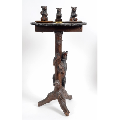 882 - A late 19th/early 20th century Black Forest carved wood smokers stand, the top surmounted three bear...