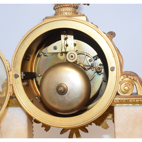 697 - A clock garniture, the clock having a 10 cm diameter enamel dial with Arabic numerals, fitted an eig...