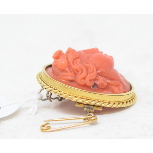 499 - A late 19th century oval coral brooch, carved in relief with a ladies head, in a yellow coloured met...