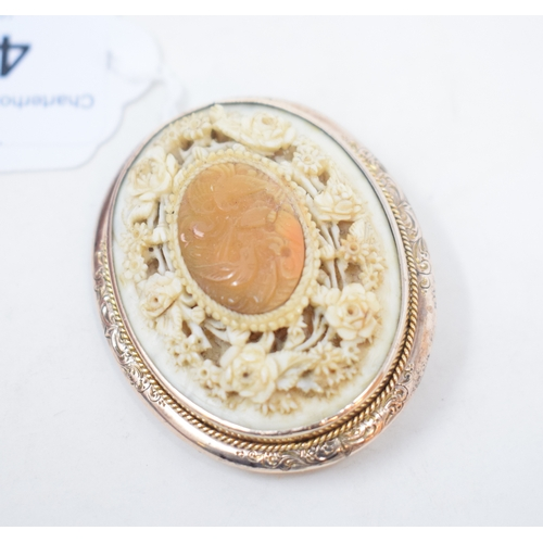 410 - A late 19th/early 20th century gold and carved ivory oval brooch...