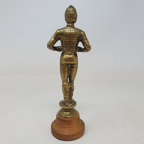 443 - A brass jockey car mascot, 13.5 cm high, on a later turned wood base, 16.5 cm high (overall)