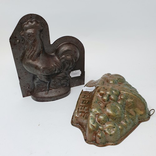 63 - A 19th century cast iron miniature fireplace, 30 x 28 cm, and two cast metal jelly molds (3)