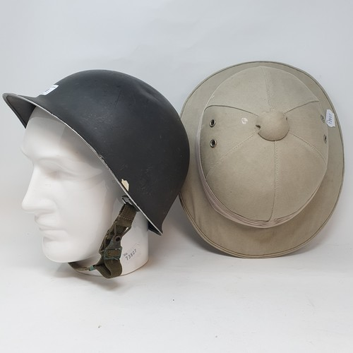 68 - A German WWII helmet, a safari pith helmet, and a porcelain head hat stand (3)
