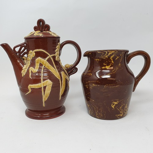 83 - A Dicker three handled jug, 18 cm high, a slip glazed jug, decorated mushrooms, 25 cm high, three ju...