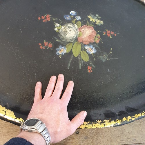 88 - A 19th century papier-mâché oval tray, painted flowers, highlighted in gilt, 78 cm wide