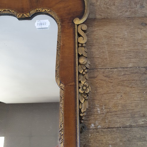 107 - A George III style walnut and giltwood wall mirror, with a shell finial, and base with candle stand,...
