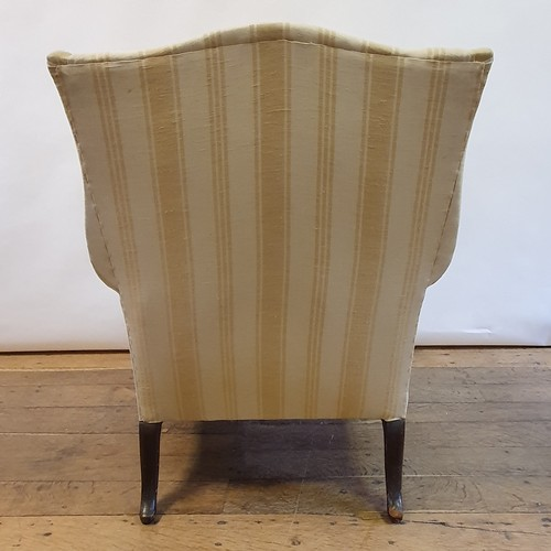 256 - A George III style wingback armchair, on mahogany cabriole legs to claw and ball feet