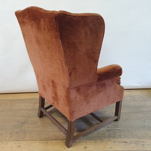 259 - A wing back armchair, on mahogany legs